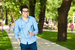 Man smiling and listening to music in the park Royalty Free Stock Image