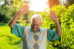 Man smiling and looking down. Senior male with raised arms. You got me. Cunning plan didn't work Stock Image