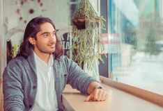 Man smiling looking through the window thoughtful daydreaming royalty free stock photos