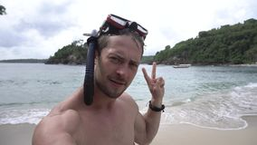 Man smiling and making selfie wearing a diving mask on ocean beach. In Nusa Penida island, Indonesia stock video footage
