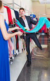 Man smiling and offering dresses in women clothing store Royalty Free Stock Photography