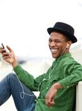 Man smiling outdoors with mobile phone. Portrait of a young man smiling outdoors with mobile phone and earphones Royalty Free Stock Photography