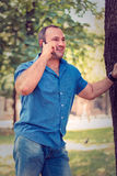Man smiling on the phone. While leaning on a tree Stock Images