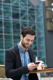 Man smiling with phone at outdoors cafe. Portrait of a young man smiling with phone at outdoors cafe royalty free stock photos