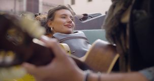Man smiling while playing guitar music with girlfriend.Woman listening to boyfriend singing song.Caucasian couple in. Love roadtrip vacation italian travel on stock video