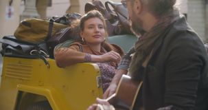 Man smiling while playing guitar music with girlfriend.Woman listening to boyfriend singing song.Caucasian couple in. Love roadtrip vacation italian travel on stock video footage
