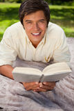 Man smiling while reading a book as he lies on a blanket Royalty Free Stock Photos