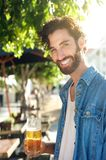 Man smiling with refreshing beer at outdoor bar in summer Royalty Free Stock Photo