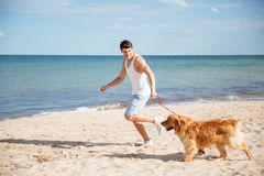 Man smiling and running with his dog on the beach stock photos