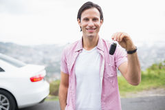 Man smiling and showing key Stock Photo