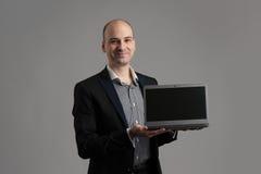 Man smiling showing laptop. Handsome man smiling showing laptop stock photography