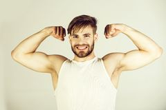 Man smiling and showing muscular arms. Man or smiling bearded athlete or strong bodybuilder showing muscular arms with muscle triceps biceps in white shirt on stock photo