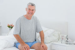 Man smiling while he is sitting on bed Stock Images