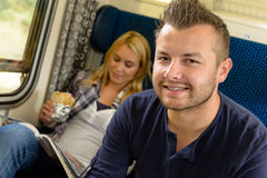 Man smiling sitting on train woman sandwich Royalty Free Stock Photos