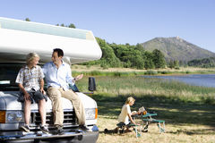 Man smiling at son (10-12) on bonnet of motor home by lake, mother reading in background Stock Image