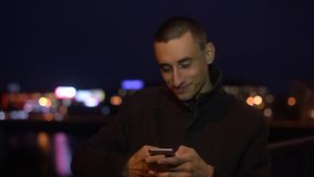 Man smiling while taking selfie or photo of view outdoors at night light. Man sms texting using app on smart phone at night stock video