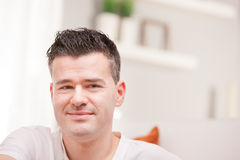 Man smiling to camera relaxing in his living room Stock Photos