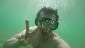 Man Smiling Under Water and Shows Peace Sign stock video