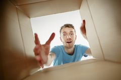Free Man Smiling, Unpacking And Opening Carton Box And Looking Inside Stock Photography - 123720562