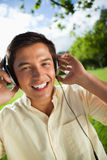 Man smiling while using headphones to listen to music in a park Royalty Free Stock Photos