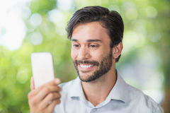 Man smiling while using his mobile phone Stock Photos