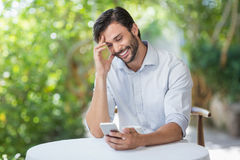 Man smiling while using his mobile phone Stock Image