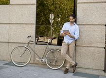 Man smiling using internet with digital tablet pad on vintage cool retro bike Royalty Free Stock Photo