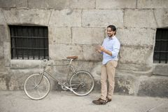 Man smiling using internet with digital tablet pad on vintage cool retro bike Stock Photography