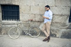 Man smiling using internet with digital tablet pad on vintage cool retro bike Royalty Free Stock Photography