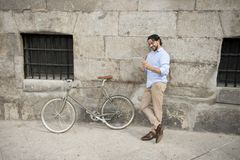 Man smiling using internet with digital tablet pad on vintage cool retro bike Stock Photos