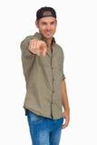 Man smiling and wearing baseball hat backwards and pointing Royalty Free Stock Photo
