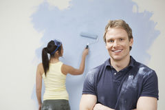 Man Smiling With Woman Painting Wall At Home. Portrait of confident young man smiling with woman painting wall at home Stock Photos