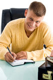 Man smiling while writing. In an office Stock Photos