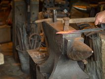 Man smithing a red-hot piece of metal on an anvil stock image