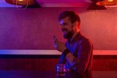 The man smoke an electronic cigarette at the vape shop. Vape bar royalty free stock photography