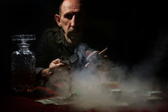 Man smoke pipe and play poker. Old mustachioed man playing poker at the table royalty free stock image