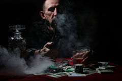 Man smoke pipe and play poker. Old mustachioed man playing poker at the table stock images