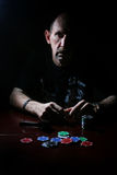 Man smoke pipe and play poker. Portrait of a person in a particular situation during the day royalty free stock image