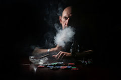 Man smoke pipe and play poker. Portrait of a person in a particular situation during the day royalty free stock photo