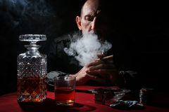 Man smoke pipe and play poker. Textured very old man with a straight face in the form of a player from the ranch stock images