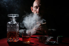 Man smoke pipe and play poker. Textured very old man with a straight face in the form of a player from the ranch stock photography