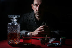 Man smoke pipe and play poker. Textured very old man with a straight face in the form of a player from the ranch stock photo