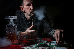 Man smoke pipe and play poker. Textured very old man with a straight face in the form of a player from the ranch stock photos