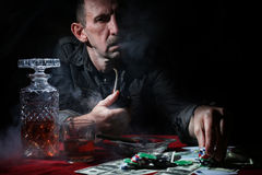 Man smoke pipe and play poker. Textured very old man with a straight face in the form of a player from the ranch royalty free stock photos