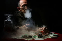 Man smoke pipe and play poker. Textured very old man with a straight face in the form of a player from the ranch royalty free stock photography