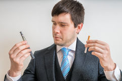 Man (smoker) is comparing classic tobacco cigarette and electronic cigarette or vaporizer Stock Photos