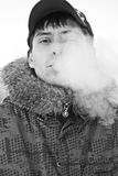Man smokes. Man lets a cloud of smoke  from cigarettes Royalty Free Stock Photos