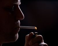 The man smokes a cigarette. Against a dark background Stock Image