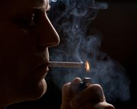 The man smokes a cigarette. Against a dark background Stock Photos