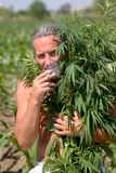 A man smokes a cigarette in the marijuana branches Royalty Free Stock Photography